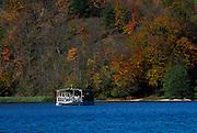 Boat on lake, autumn coloured trees in background. Plitvice National Park, Croatia