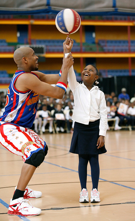 In this photo from the Harlem Globetrotters, Racine McEachin, 9, a 3rd grader from P.S. 36 gets a helping hand from Scooter Christensen during a break at the Harlem Globetrotters' 3rd annual game for local school children at the 369th Harlem Armory Center in New York, Monday, Oct. 5, 2009. (Photo Harlem Globetrotters/Stuart Ramson)