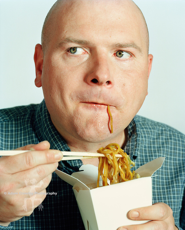 Man eating noodles, looking away