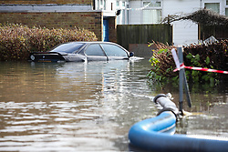 © Licensed to London News Pictures. 25/02/2014. Basingstoke, Hampshire, UK. A BMW car surrounded by flood water on Grampian Way in the Buckskin area of Basingstoke, Hampshire. Groundwater levels are continuing to rise slowly in the area, where many homes have been evacuated. Water is still being pumped by tankers, and taken to nearby sewerage plants. Photo credit : Rob Arnold/LNP