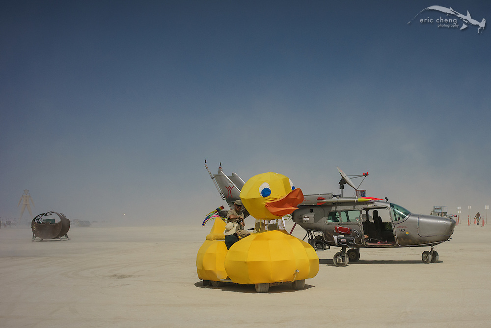 Yellow ducky art car and a helicopter art car. Burning Man 2014