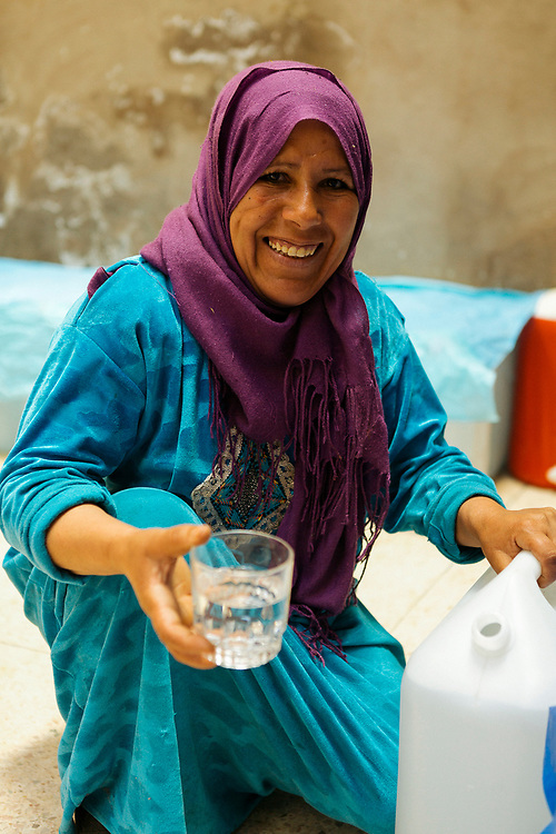 KELAAT M'GOUNA, MOROCCO - 14TH MAY 2016 - Member at Association Feminine du Dades, shows a group of tourists around the cooperative which produces distilled rose water.