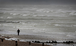 DATE CORRECTION© Licensed to London News Pictures. 20/11/2016. Lancing, UK. A walker braves the wind and waves of Storm Angus as she walks on the beach at Lancing. The south east has experienced winds of up to 80 miles per hour as the first named storm of the season hits. Photo credit: Peter Macdiarmid/LNP