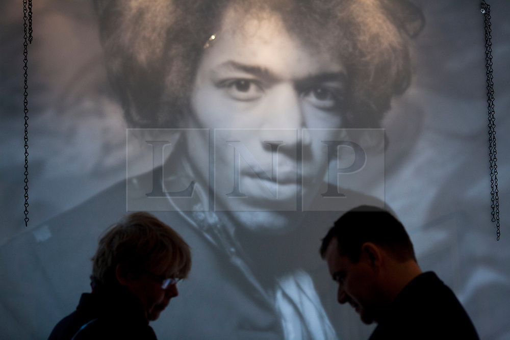 © Licensed to London News Pictures. 02/04/2013. London, UK. A huge Jimi Hendrix poster looks down on fans browsing merchandise in a pop-up shop set up to celebrate a new album by the late guitar legend in London today (02/04/2013). The shop, called 'People, Hell and Angels', located near London's Carnaby Street, runs from the 1st of April until the 12th of April 2013 and features memorabilia, music and photographs of the guitarist and singer who died in 1970 of a drug overdose. Photo credit: Matt Cetti-Roberts/LNP
