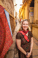 A middle aged woman posing for a picture in the narrow streets of Jaisalmer, Jaisalmer Fort, Rajasthan, India.