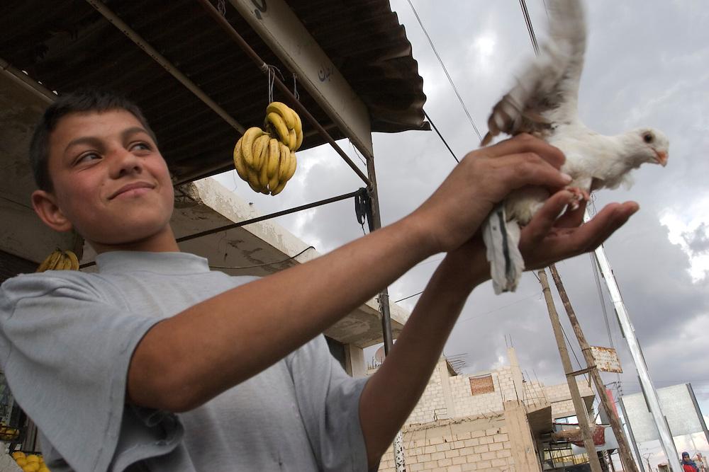 Un niño juega con una paloma en un pueblo en las afueras de Damasco.