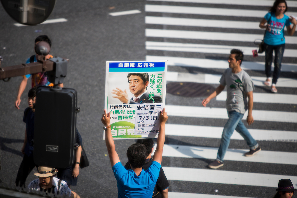 TOKYO, JAPAN - JULY 03 : A man with poster of Japanese Prime Minister Shinzo Abe walking around crossing Shibuya before the election campaign of Liberal Democratic Party in Shibuya crossing, Tokyo prefecture, Japan, on July 3, 2016. Photo: Richard Atrero de Guzman