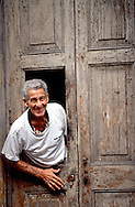 Old man leans out the front door of his house smiling in Havana, Cuba