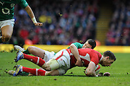 Alex Cuthbert of Wales is tackled by Ireland's Jonny Sexton. RBS Six nations championship, Wales v Ireland at the Millennium stadium in Cardiff, South Wales on Saturday 2nd Feb 2013. pic by Andrew Orchard, Andrew Orchard sports photography,