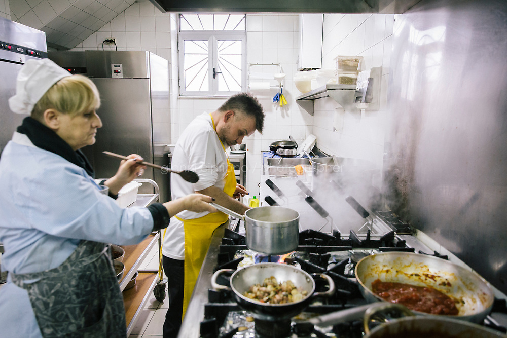 NAPLES, ITALY - 20 MARCH 2018: (L-R) Rita and Carmine Esposito are seen here cooking in the kitchen of the Pizzeria e Trattoria Vigliena in Naples, Italy, on March 20th 2018.<br /> <br /> Pizzeria e Trattoria Vigliena is a restaurant outside of the city center and adjacent to the port. At lunch, the place is packed with workers from the docks and ship owners and workers from the recently built Marina Vigliena.<br /> <br /> The restaurant is owned by Raffaele Esposito, Concetta&rsquo;s son and the third generation of a family of chefs who founded this restaurant in the middle of the 20th century