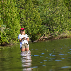 A teenage girl fly-fishing in Island Pond at Red River Camps in Aroostook County, Maine. Deboullie Public Reserve Land.