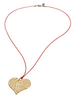 love inscribed gold heart on a red strand necklace