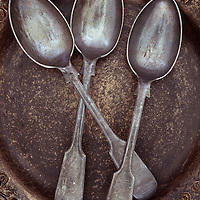 Three antique tarnished silver teaspoons lying in brown and gold bowl with ornate pattern