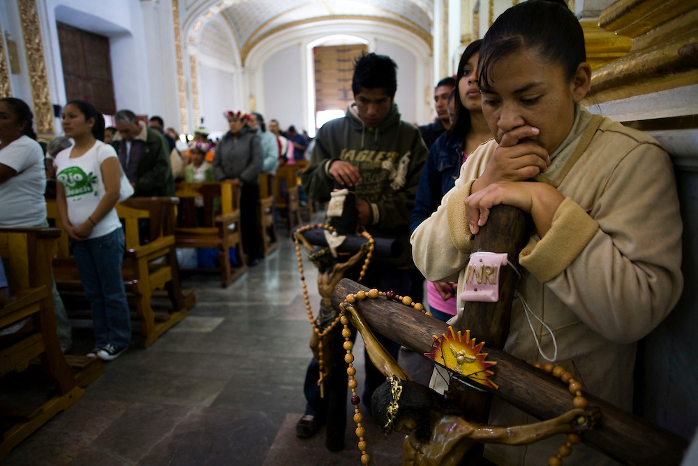 Mireye Velasquez, 34, prays during mass at the church in Chalma.  Chalma is the second most important pilgrimage site in Mexico.  People come from all over the country to visit the Senor de Chalma. They often arrive wearing crowns made of flowers, and leave the crowns at the church.