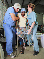 Physical therapists  Jeff Hills of Jacksonville (left) and Kat MacKirdy of West Newton, MA, (right) help Annette Plezemon stand for the first time since the earthquake a month prior.
