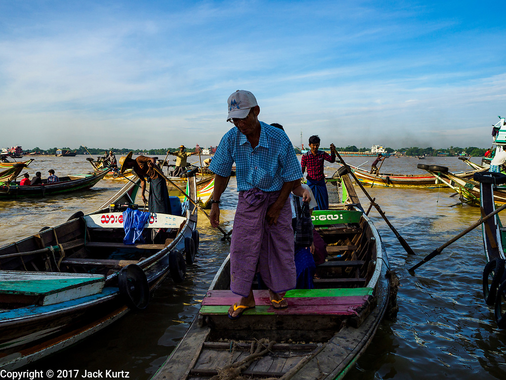 23 NOVEMBER 2017 - YANGON, MYANMAR: Passengers get off water taxis at the San Pya Fish Market Pier. San Pya Fish Market is one of the largest fish markets in Yangon. It's a 24 hour market, but busiest early in the morning. Most of the fish in the market is wild caught but aquaculture is expanding in Myanmar and more farmed fresh water fish is being sold now than in the past.    PHOTO BY JACK KURTZ