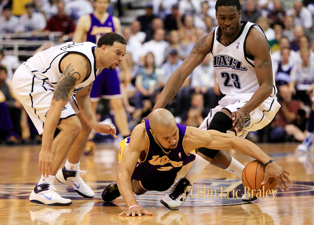 Los Angeles Lakers guard Derek Fisher (2) goes after a loose ball as Utah Jazz players Deron Williams, left, and Wesley Matthews, right, defend during the first half of Game 3 of the NBA Western Conference second-round playoff series in Salt Lake City, Saturday, May 8, 2010. (AP Photo/Colin E Braley)