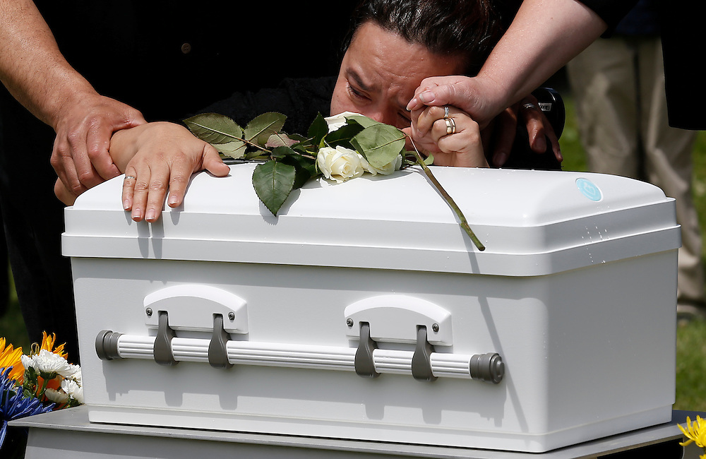 The grandmother of baby Angel Antonio cries on his casket during a burial service at All Saints Cemetery in Des Plaines, Illinois, United States, June 19, 2015. More than a year after he was found dead in a plastic shopping bag on a Chicago sidewalk, the baby boy was buried by a non-profit group &quot;Rest in His Arms&quot; after being abandoned by his teenage mother, who is charged with murder. Picture taken June 19, 2015. <br />