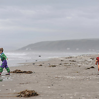 Two children playing on a beach in winter with headland and stormy seas