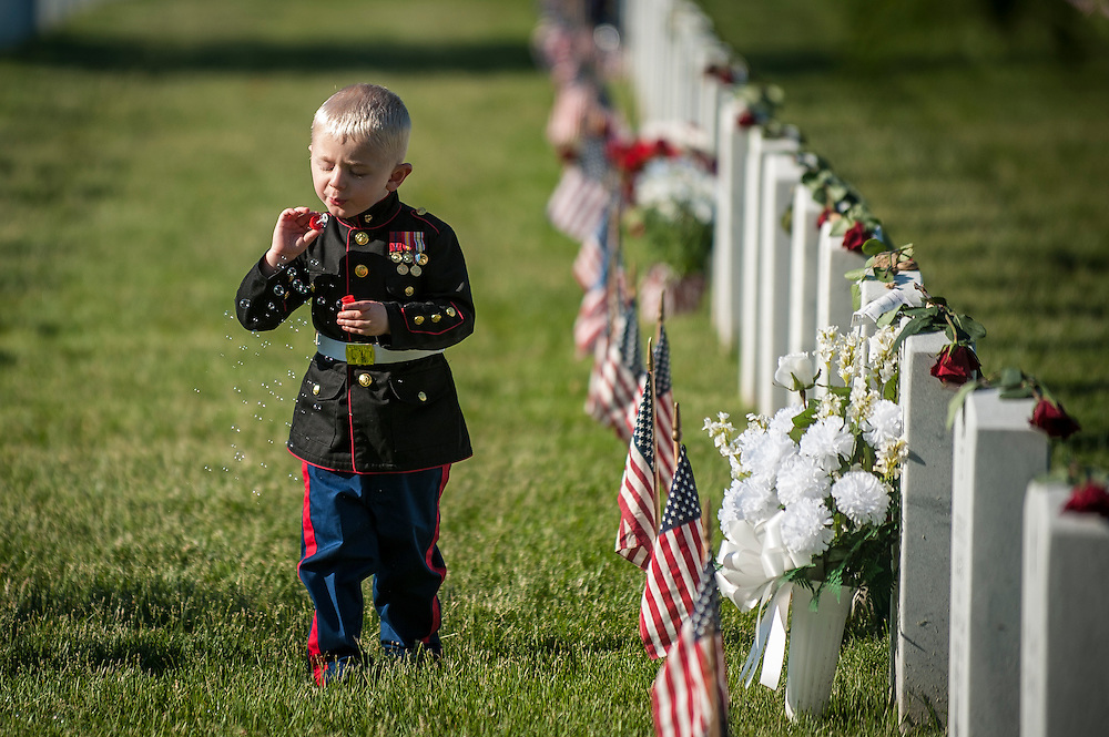 On Memorial Day, Christian Jacobs, 3, of Hertford, North Carolina, blows bubbles at the gravesite of his father, Marine Sgt. Christopher Jacobs at Arlington National Cemetery in Arlington, Virginia, USA, on 26 May 2014.