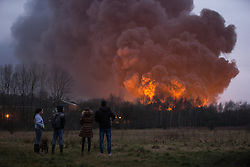 """© Licensed to London News Pictures . 15/03/2015 . Salford , UK . People watch the fire burning from a nearby park . Roads are closed and people have been evacuated as a large fire burns at a unit within """" Junction Eco-Park """" in Clifton , Greater Manchester , this evening (Sunday 15th March 2015) . The smoke and flames can be seen for many miles . Forty fire fighters are at the scene working to control the blaze . Photo credit : Joel Goodman/LNP"""