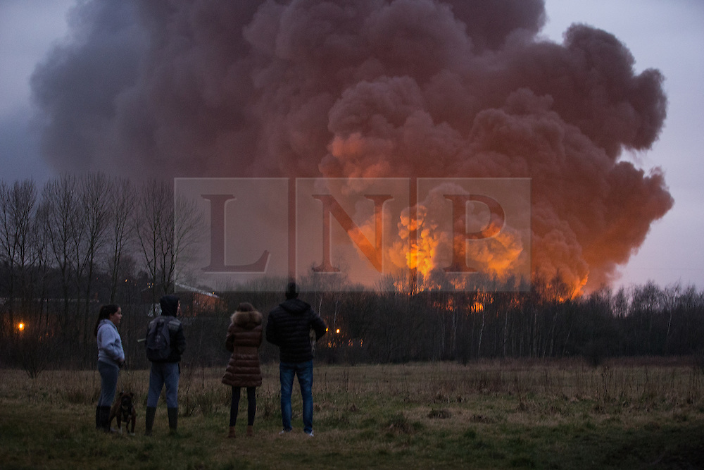 "© Licensed to London News Pictures . 15/03/2015 . Salford , UK . People watch the fire burning from a nearby park . Roads are closed and people have been evacuated as a large fire burns at a unit within "" Junction Eco-Park "" in Clifton , Greater Manchester , this evening (Sunday 15th March 2015) . The smoke and flames can be seen for many miles . Forty fire fighters are at the scene working to control the blaze . Photo credit : Joel Goodman/LNP"