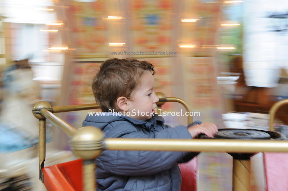 Young child on a merry go round with panning effect. Model released