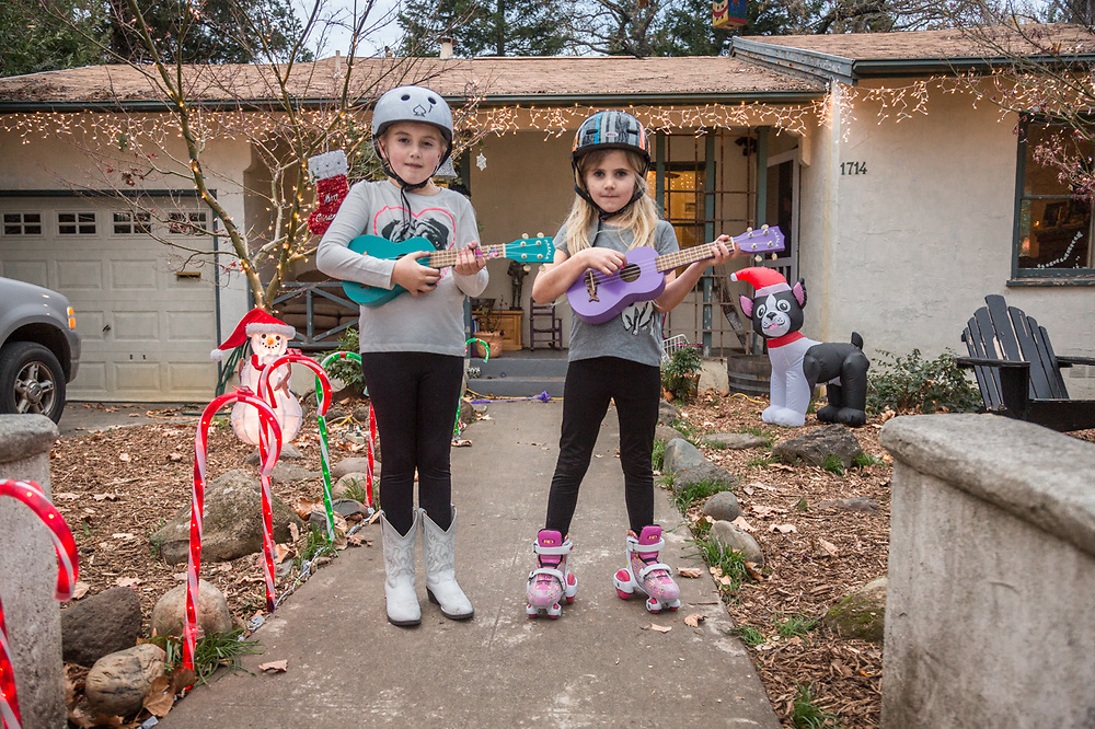 """We got these for Christmas...we're taking lessons at school.""  -Sisters Lola and Lucia practice their ukuleles in front of their  home on Cedar Street in Calistoga"