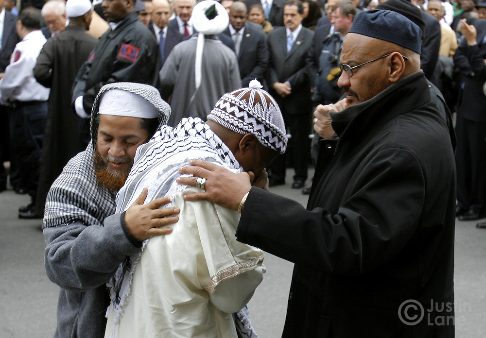 Men consol each other at the end of funeral services for the ten people killed in a recent house fire at the Islamic Cultural Center in the Bronx, New York on Monday 12 March 2007. Of the ten people killed in the fire, 9 were children, and all were immigrants from Mali.