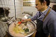 Marcus Dirr, a master butcher, mixes herbs, spices and other ingredients to make sausages at his shop in Endingen, near Freiburg im Breisgau, Germany.   (Marcus Dirr  is featured in the book What I Eat: Around the World in 80 Diets.)  The caloric value of his typical day's worth of food in March was 4600 kcals. He is 43 years of age; 5 feet, 9 inches tall; and 160 pounds. The Dirrs know the farmers who supply their animals, and in fact hand choose the animals and watch them grow. MODEL RELEASED.