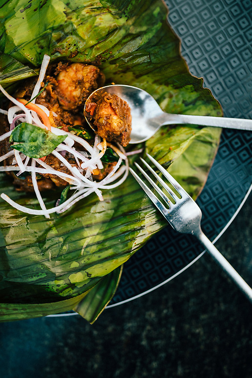 Fort Kochi, India -- February 14, 2018: Shrimp and curry paste grilled in banana leaf at the Taj Malabar hotel.