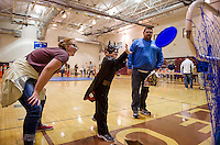 "Johanna Morris and Scott Canning watch as ""Batman"" Brady Canning plays the Frisbee Game during Friday evenings Halloween Party at Gilford Middle School.  (Karen Bobotas/for the Laconia Daily Sun)"