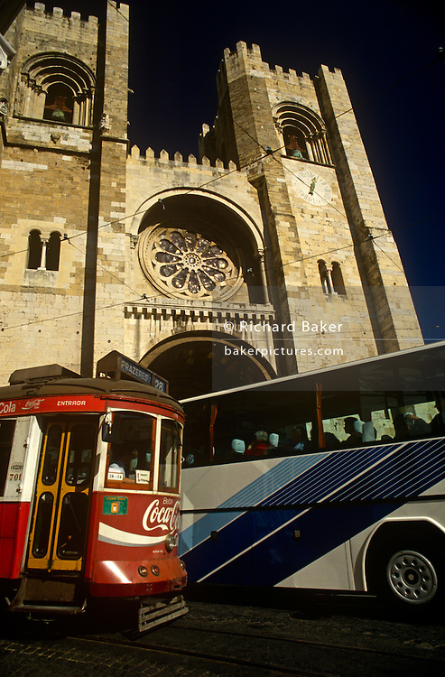 Old tram clashes on narrow street with more modern tourist coach below the towering Se Cathedral in central Lisbon.