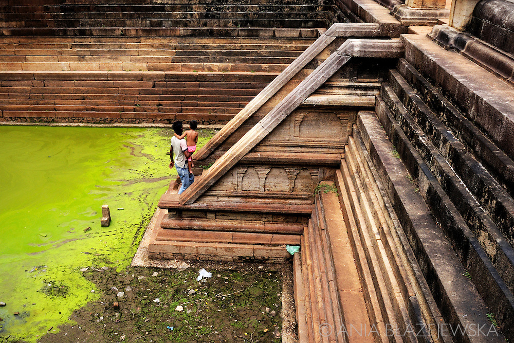 Sri Lanka, Anuradhapura. Man carrying a child on the stairs of one of Twin Ponds.