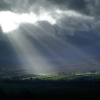 Fields lit with rays from the sun under a dark stormy sky in England