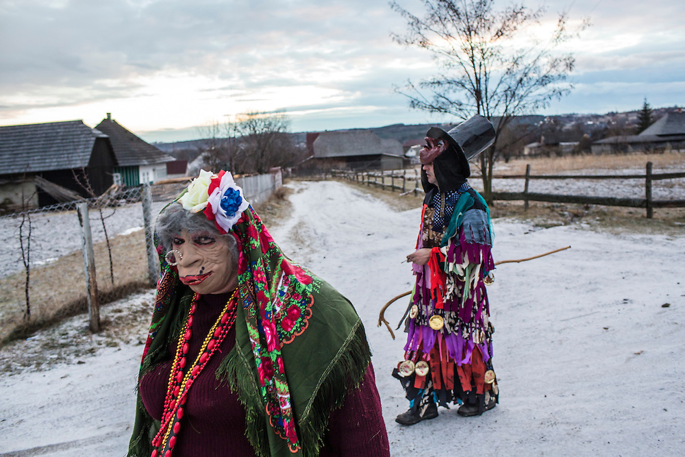 Grygory Pleshka, 28, left, wearing the costume of an old woman, and another man celebrate the Malanka Festival on Thursday, January 14, 2016 in Krasnoilsk, Ukraine. The annual celebrations, which consist of costumed villagers going in a group from house to house singing, playing music, and performing skits, began the previous sundown, went all night, and will last until evening. According to tradition, married men may only participate in Malanka while wearing a mask.