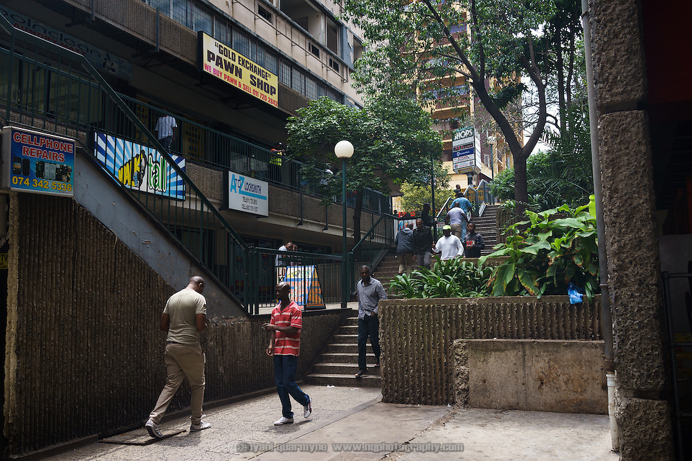People walk down the stairs past a pawn shop towards the entryway to the only shopping centre in Hillbrow, an inner-city nighbourhood in Johannesburg, South Africa with a reputation for drugs, crime and violence.