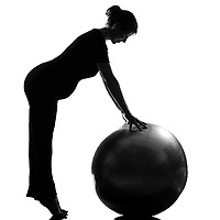 beautiful caucasian pregnant woman exercising fitness workut pilates with fitness ball in full length silhouette on studio isolated white background