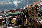Sand dredgers look on as conveyor belts move sand from the dredging boats to the shore for drying. The dredged sand is sold locally and to large scale construction sites in nearby major cities such as Kunming and Jinhong.