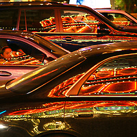 A vehicle passenger stares out the window at the bright lights of the Vegas Strip, as reflected in vehicle windows in Las Vegas, NV, May 8, 2010.