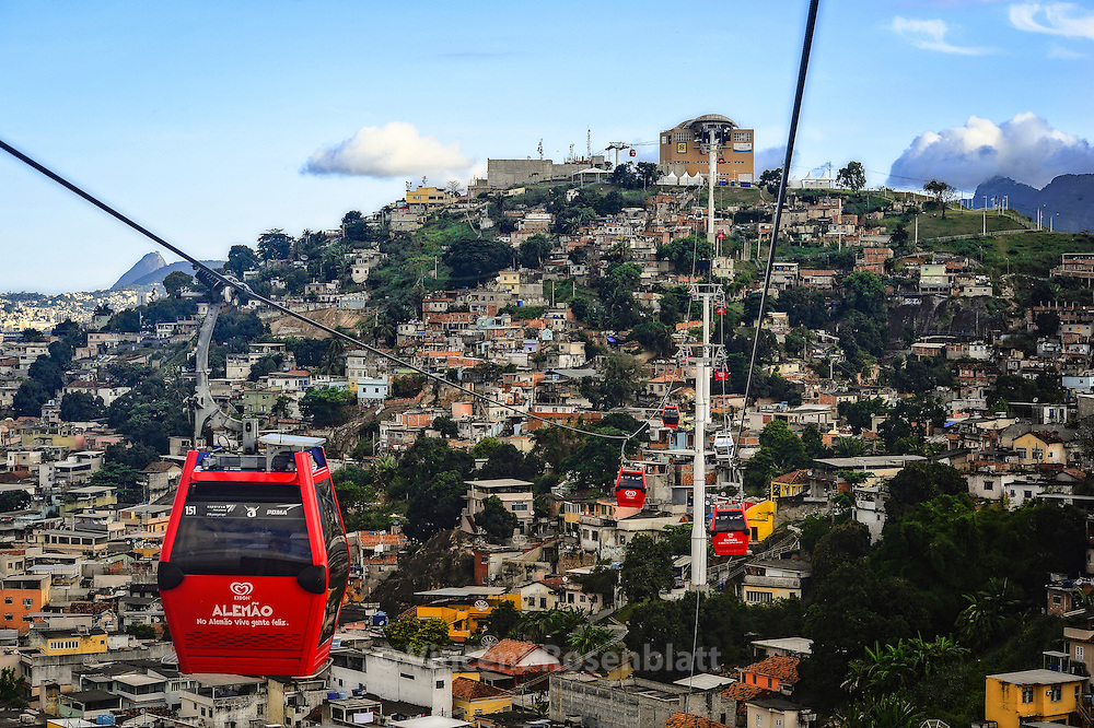 Cable Car connecting all hills and favelas of the Complexo do Alemão. One dollar for the most amazing urban landscapes from Zona Norte of Rio de Janeiro. n the background, left, the Sugarloaf, in zona sul - the other cable car attraction from Rio.