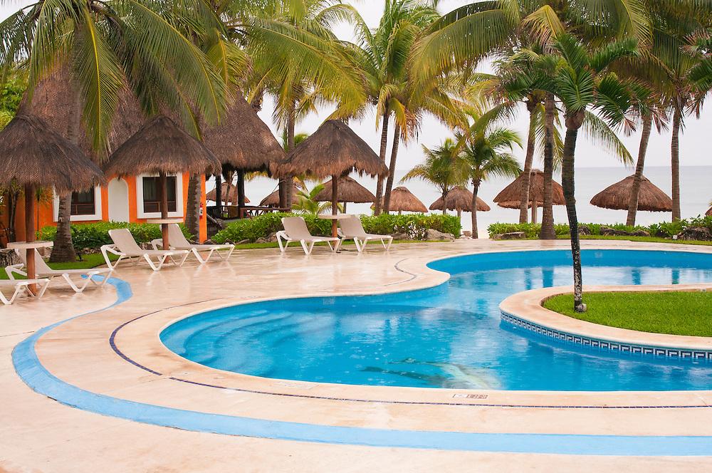 Mahekal Resort swimming pool, guest room and palapas; Playa del Carmen, Riviera Maya, Mexico.