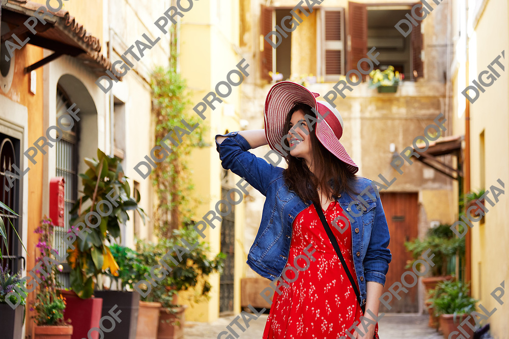 Smiling pretty tourist woman holding hat and looking away at Trastevere in Rome, Italy.
