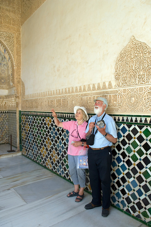 SPAIN: Andalucia..The Alhambra Palace in Granada: details of latticework and fretwork in the Courtyard of the Myrtles, the Comares Palace.Elderly tourists