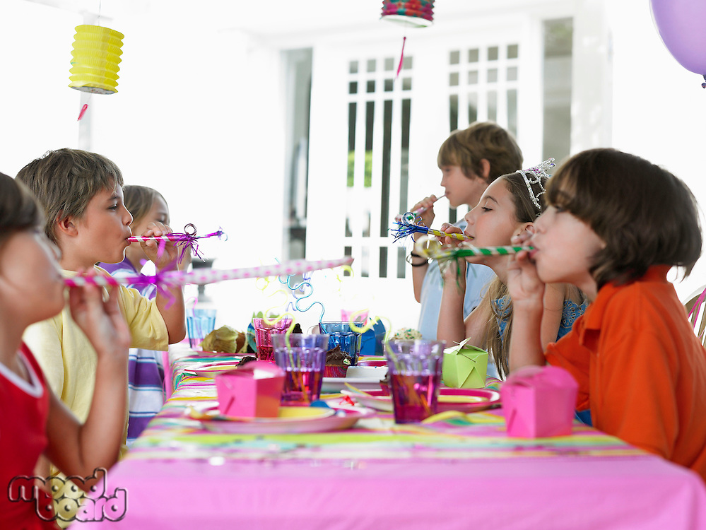 Six children (7-12) at table blowing party puffers side view