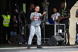 © Licensed to London News Pictures . 12/08/2018. Manchester , UK . POSITIVE PLATINUM performs on stage . The second day of the annual Caribbean Carnival in Alexandra Park in Moss Side , celebrating music , food and Afro-Caribbean culture . A nearby shooting overnight lead to at least ten people injured . Ten people are in hospital . Photo credit : Joel Goodman/LNP