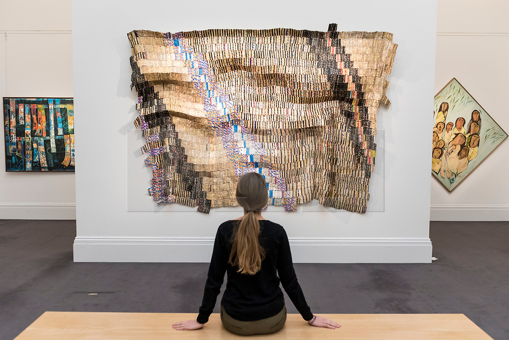 "© Licensed to London News Pictures. 29/03/2019. LONDON, UK. A staff member views ""Zebra Crossing 2"", 2007, by El Anatsui (Est. GBP 550,000-750,000). Preview of Sotheby's upcoming Modern and Contemporary African Art sale.  Works from artists across the African diaspora will be offered for sale on 2 April.  Photo credit: Stephen Chung/LNP"