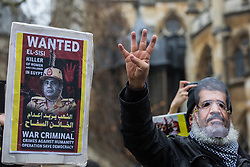 London, UK. 25 January, 2020. A man wearing a mask bearing the image of the late Egyptian President Mohamed Morsi makes the R4bia hand sign at a protest outside Parliament against the Egyptian government of President Abdel Fattah el-Sisi by supporters of the Egyptian Revolutionary Council and UK anti-Coup organisations.