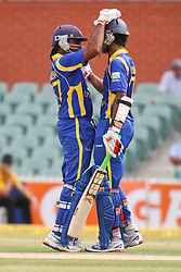© Licensed to London News Pictures. 14/02/2012. Adelaide Oval, Australia. Sri Lankan batsman Dinesh Chandimal (left) is congratulated by his captain Mahela Jayawardena after making 50 during the One Day International cricket match between India Vs Sri Lanka. Photo credit : Asanka Brendon Ratnayake/LNP