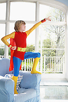 Young boy (7-9) wearing superman costume standing on armchair and pointing